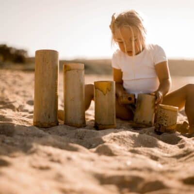 kid playing with bamboo in sand